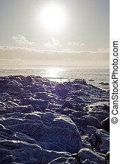 waves over white sunset rocks