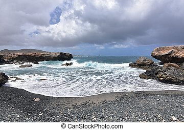Waves Receding on the Black Pebble Beach in Aruba