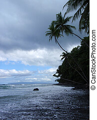 Waves roll across beach in cloudy weather at dawn in Punta Banco, Costa Rica, Central America