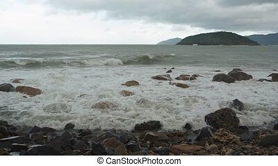 Ocean waves roll and break over a rocky stretch of tropical beach in Vietnam on a gray and overcast day.