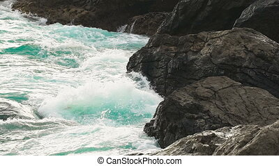waves rolled on shore stone, broken and hissing. Foam and...
