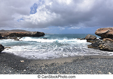 Waves Rolling Onto the Black Sand Stone Beach in Aruba