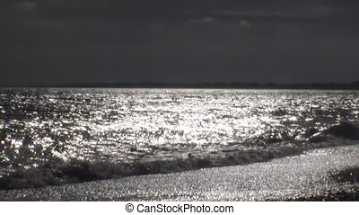 Waves run ashore. The shimmering waves in the sun. Video shot backlight. The sun reflected in the water of the English Channel near Barton on Sea.