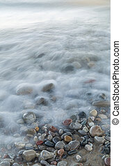 Waves rushing over stones on a Lake Huron beach - Ontario, Canada