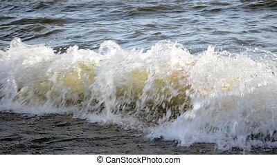 Waves splash on pebble sea shore