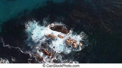 Waves splashing o the rocks amidst the sea 4k - Aerial of...