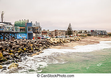 Waves, stones at the coastline with houses in background, Swakopmund German colonial town, Namibia