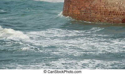 Waves strike the stone wall
