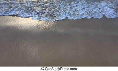 Waves surf on a beach at the evening
