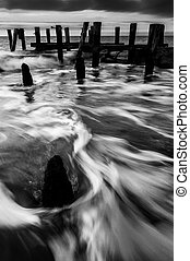 Waves swirl around pier pilings in the Delaware Bay at sunset, seen from Sunset Beach, Cape May, New Jersey.