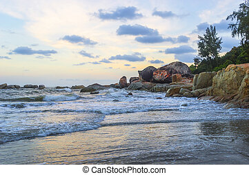 Waves to beach rock with sunset scene