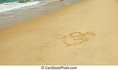 Waves touch sand with the inscription I love
