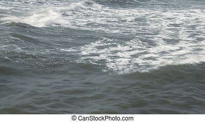 Waves touching sandy beach at sunny