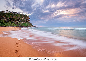 Waves wash on the seashore washing away footprints