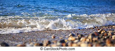 Waves washing over gravel beach, macro shot.