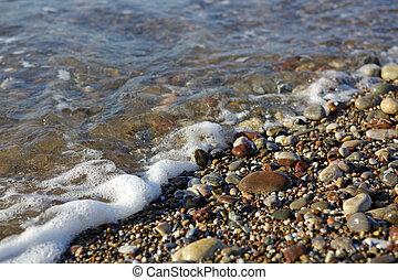 Waves washing over gravel beach, macro shot. - Sand beach ...