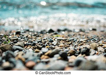 Waves washing over gravel beach, macro shot with narrow ...