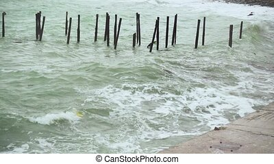 Waves with garbage are broken on a concrete slab on the shore