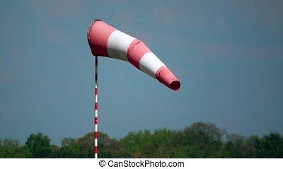 Waving airport weather vane or wind flag 4K telephoto lens shot