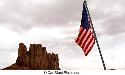 Waving American Flag in the Monument Valley at sunset, Arizona.