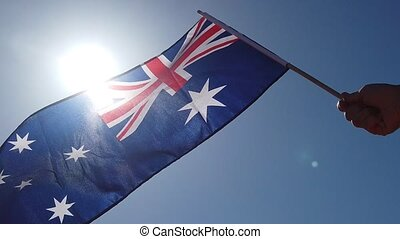 SLOW MOTION close up of waving Australian flag against the sun in the blue sky background. Red Centre in Northern Territory, Australia.