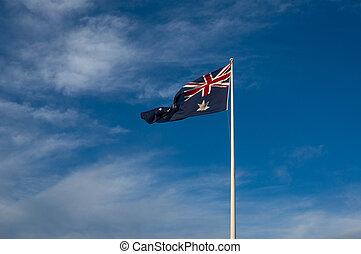 Australian national flag against blue sky on the background