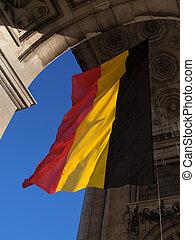 Belgian flag waving under the triumphal arch in the Parc du Cinquantenaire in Brussels.