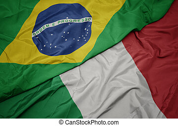 waving colorful flag of italy and national flag of brazil.