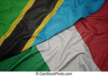 waving colorful flag of italy and national flag of tanzania. macro