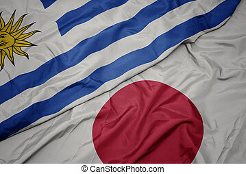 waving colorful flag of japan and national flag of uruguay.