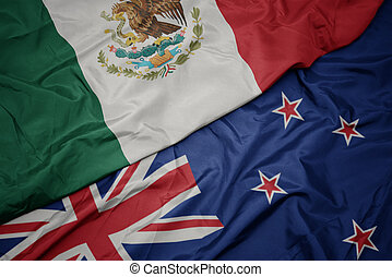 waving colorful flag of new zealand and national flag of mexico.