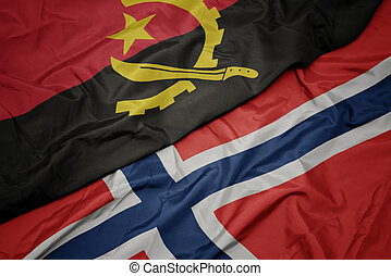 waving colorful flag of norway and national flag of angola.