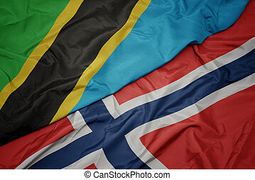 waving colorful flag of norway and national flag of tanzania.
