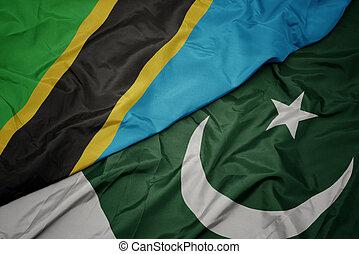 waving colorful flag of pakistan and national flag of tanzania. macro