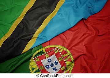 waving colorful flag of portugal and national flag of tanzania. macro