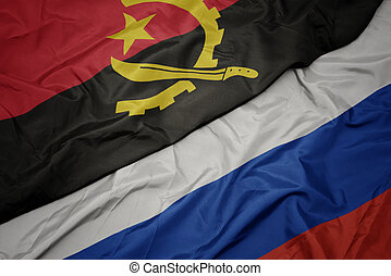 waving colorful flag of russia and national flag of angola.