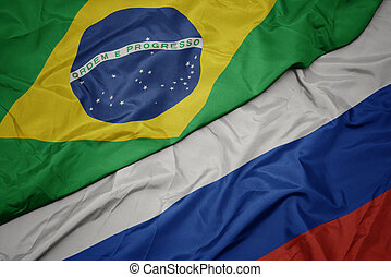 waving colorful flag of russia and national flag of brazil.