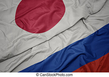 waving colorful flag of russia and national flag of japan.