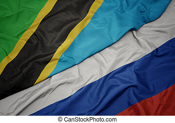 waving colorful flag of russia and national flag of tanzania.