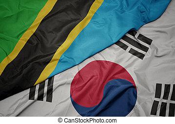 waving colorful flag of south korea and national flag of tanzania. macro