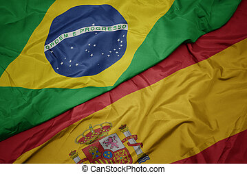 waving colorful flag of spain and national flag of brazil.