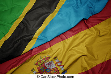 waving colorful flag of spain and national flag of tanzania.