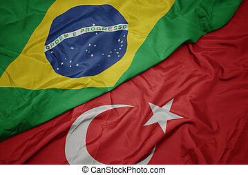waving colorful flag of turkey and national flag of brazil.