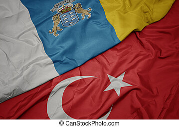 waving colorful flag of turkey and national flag of canary islands.
