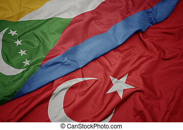 waving colorful flag of turkey and national flag of comoros.