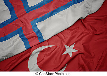 waving colorful flag of turkey and national flag of faroe islands.