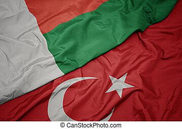 waving colorful flag of turkey and national flag of madagascar.