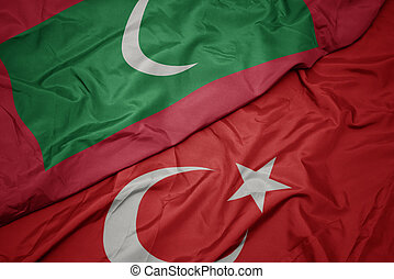 waving colorful flag of turkey and national flag of maldives.