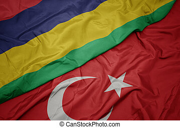 waving colorful flag of turkey and national flag of mauritius.