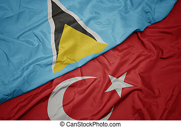 waving colorful flag of turkey and national flag of saint lucia.
